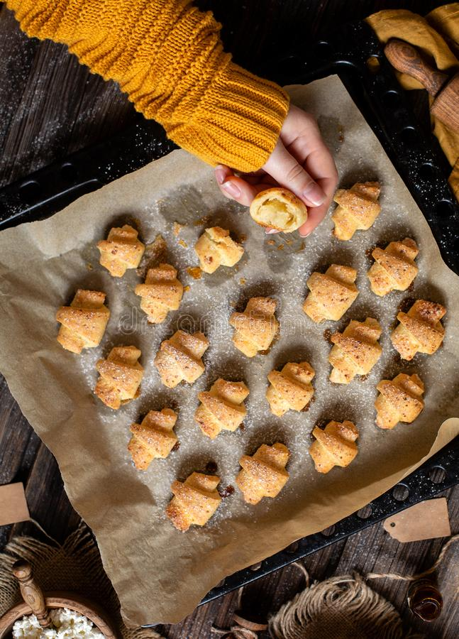 Overhead shot of tasty baked rolled or bagels cookies on baking tray with parchment. In woman hands on rustic wooden table with bowls of flour, sugar and royalty free stock photo