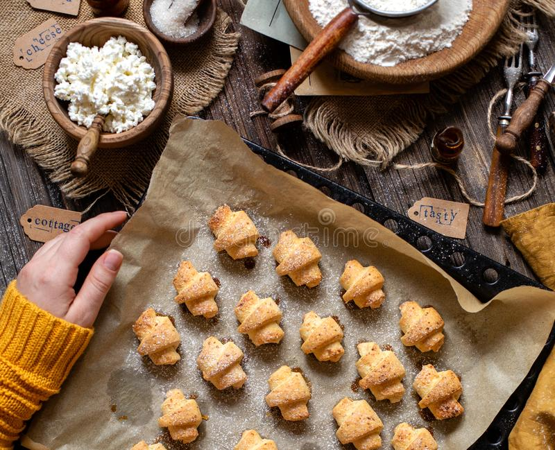 Overhead shot of tasty baked rolled or bagels cookies on baking tray with parchment. In woman hands on rustic wooden table with bowls of flour, sugar and stock photography
