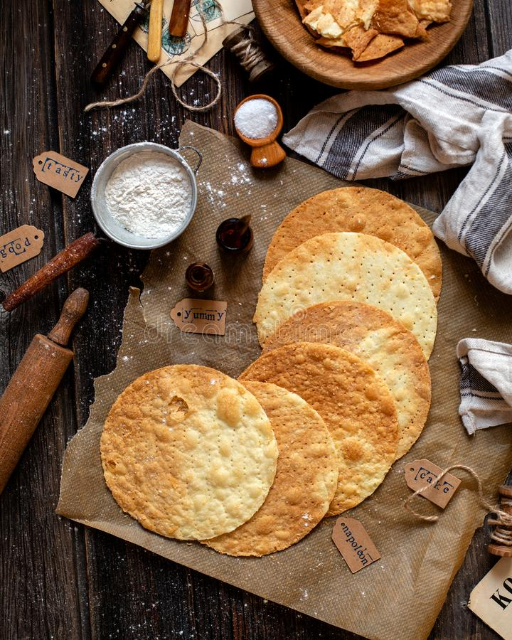 Overhead shot of tasty crispy baked round puff pastry layers of homemade traditional Russian napoleon cake. On parchment on rustic royalty free stock photos