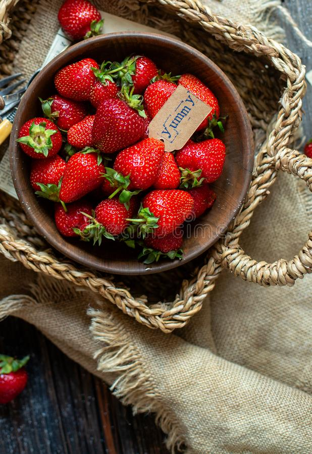 Overhead shot of tasty ripe strawberries in wooden bowl stands in wicker strawy basket on rustic table stock image