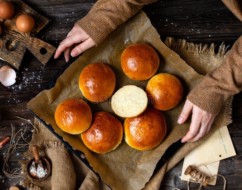Overhead shot van de homemade gesneden bakkersbroodjes op de bakbak met perkament in vrouwelijke handen royalty-vrije stock afbeeldingen