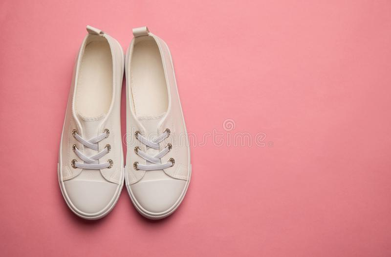 Overhead Shot Of White female Sneakers On Pastel Pink Background stock photography