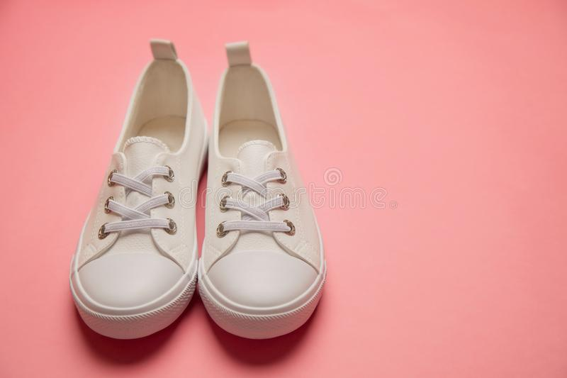 Overhead Shot Of White female Sneakers On Pastel Pink Background royalty free stock photo