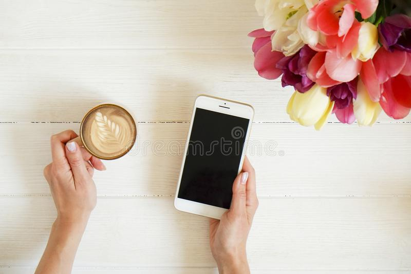 Overhead shot of woman hands holding cell phone gadget & coffee cup w cappuccino latte art on white wooden table background. Beaut royalty free stock image
