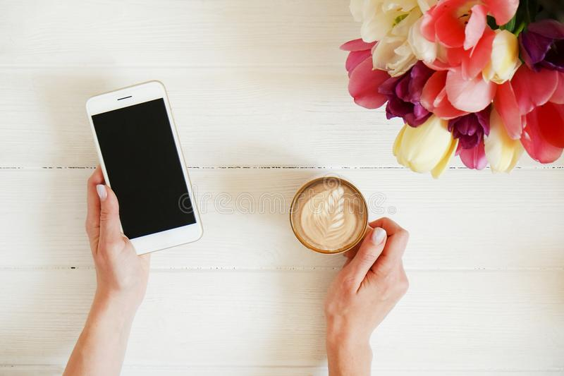 Overhead shot of woman hands holding cell phone gadget & coffee cup w cappuccino latte art on white wooden table background. Beaut royalty free stock photography