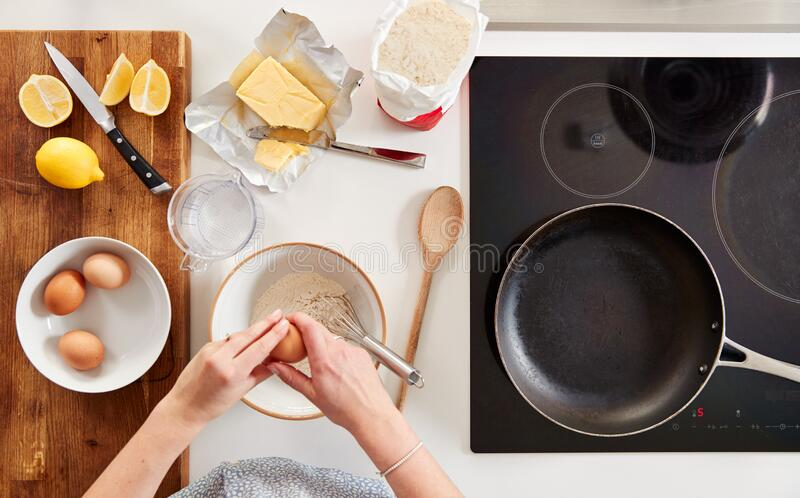 Overhead Shot Of Woman In Kitchen With Ingredients Making Pancakes Or Crepes For Pancake Day royalty free stock photography