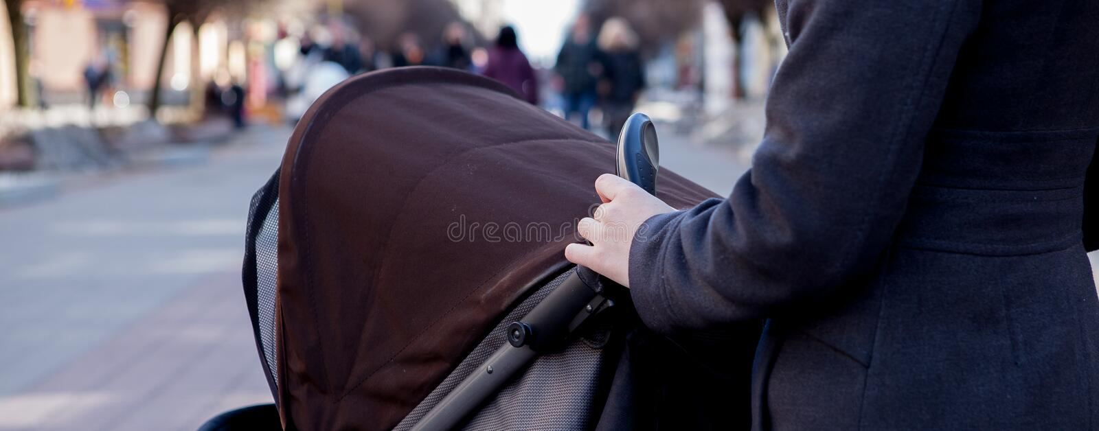 Overhead shot of young mother strolling a carriage. Hands holding stroller handle stock image