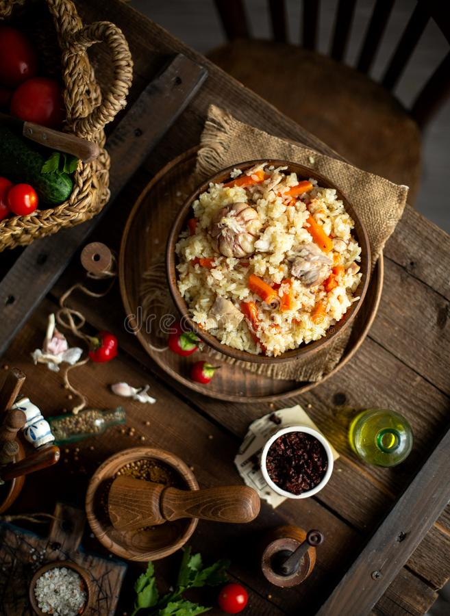 Overhead shot of yummy rice dish plot, pilaf, curry in wooden bowl stands on rustic table stock photography