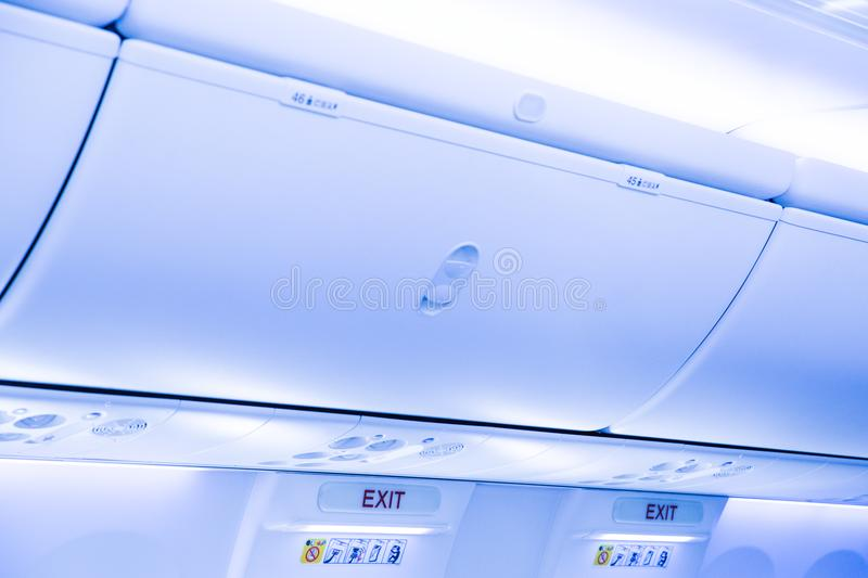 Overhead stowage or overhead bin and emergency exit door. With the exit sign at the door frame stock images