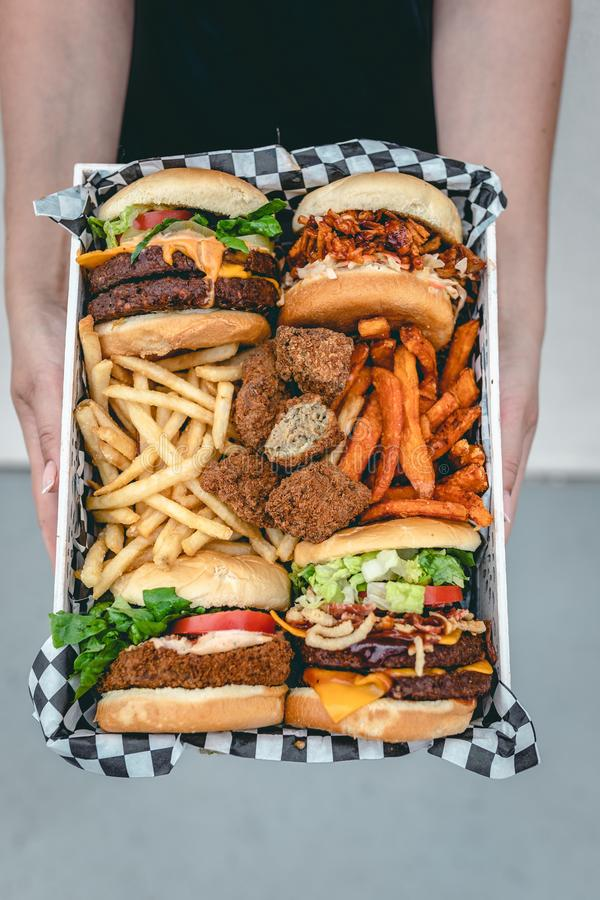 Overhead vertical shot of a female holding a basket of various junk food products stock photo