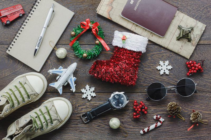 Overhead view of accessory Merry Christmas with items to travel background concept. Mix several object on the modern rustic brown wooden at home office desk royalty free stock photo
