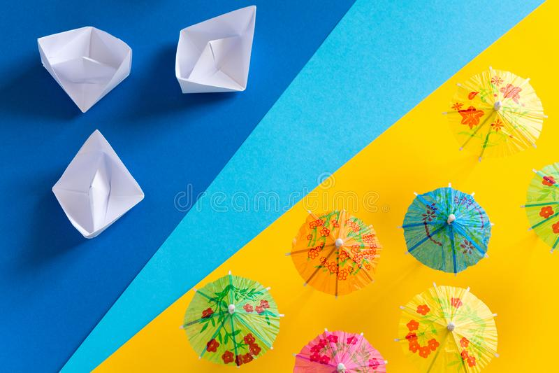 Overhead view on beach with umbrellas and sea with boats. Sea travel and summer vacation minimal concept. Paper origami stock photos