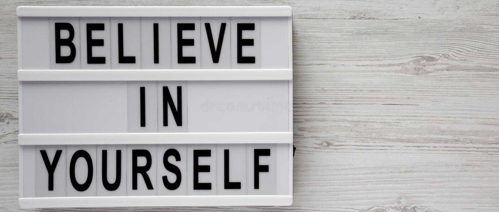 Overhead view, `Believe in yourself` words on a lightbox on a white wooden background, top view. From above, flat lay, overhead. royalty free stock photography