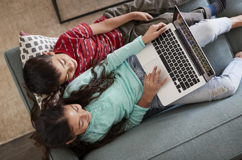 Overhead View Of Brother And Sister Sitting On Sofa At Home Having Fun Playing On Laptop Together stock images