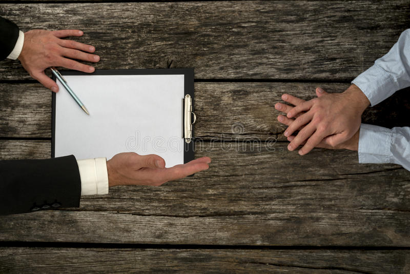 Overhead view of business employer an employee sitting at office. Desk negotiating about employment conditions as the employer offers his hand in handshake royalty free stock photo