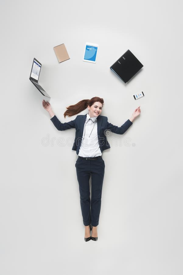 overhead view of businesswoman with various office supplies using laptop stock photography