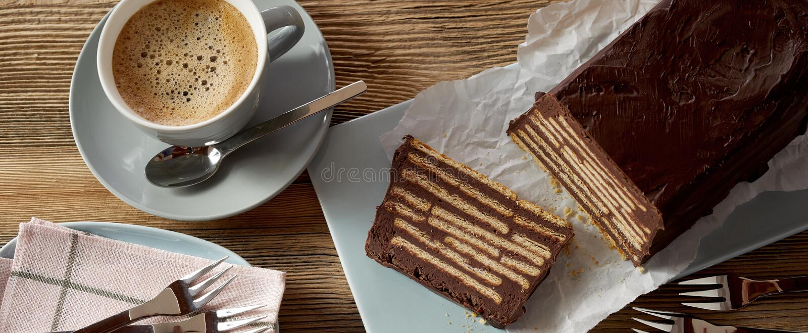 Overhead view of chocolate cake and coffee. Overhead view of chocolate iced biscuit cake with one slice cut and a blue ceramic cup of creamy coffee stock photo