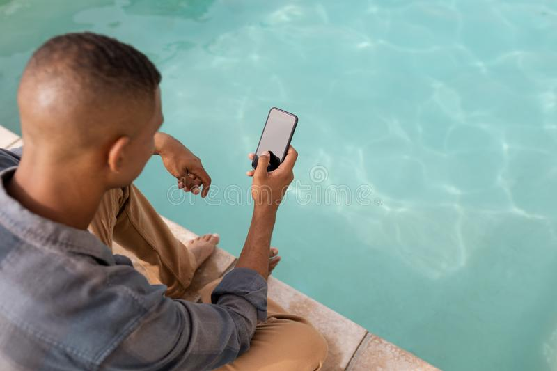 Man using mobile phone near swimming pool. Overhead view close up of handsome young mixed-race man using mobile phone near swimming pool at home stock image