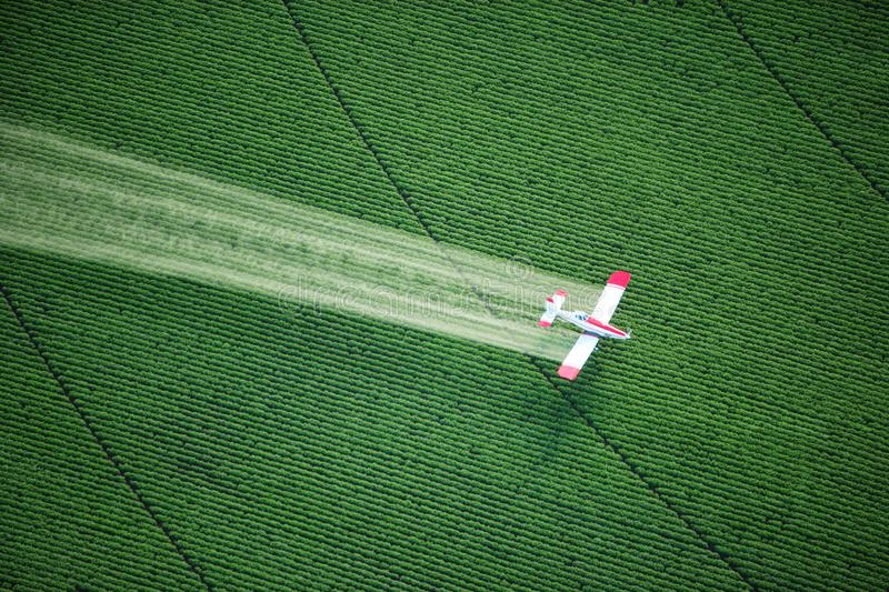 A crop duster spraying a green farm field. royalty free stock photography