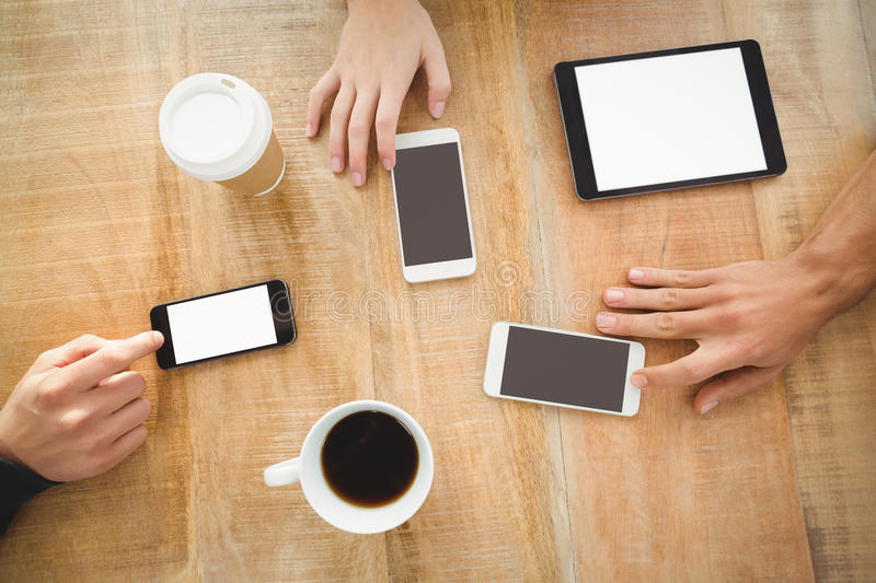 overhead view of cropped hands with mobile phones and digital tablet royalty free stock images