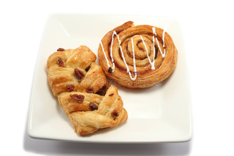 Overhead view of Danish pastries. Iced cinnamon swirl and a maple and pecan danish pastry on a square white plate stock image