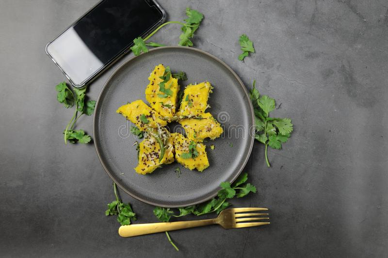 Overhead view of  Dhokla, an Indian Gujarati snack which is vegetarian. With a cellphone and copy space stock photo