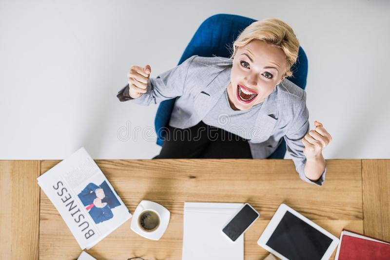 Overhead view of excited businesswoman. Looking at camera at workplace in office royalty free stock photos