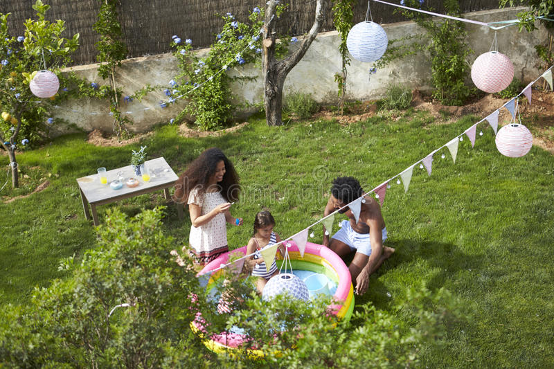 Overhead View Of Family Having Fun In Garden Paddling Pool royalty free stock photo