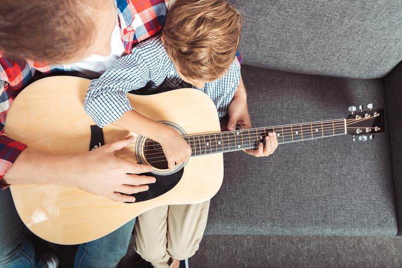 overhead view of father and son playing guitar while sitting stock photo