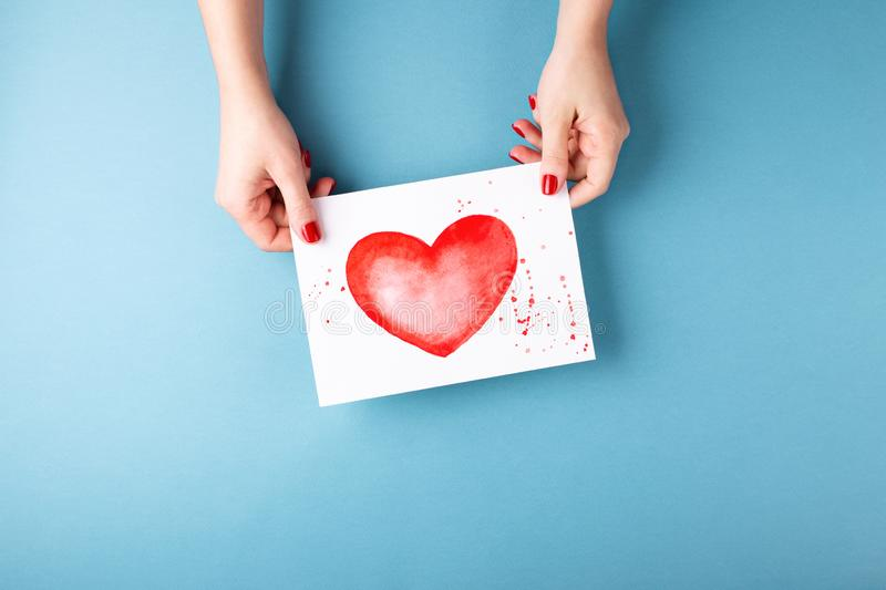 Female hands holding card with heart on blue background. stock photo