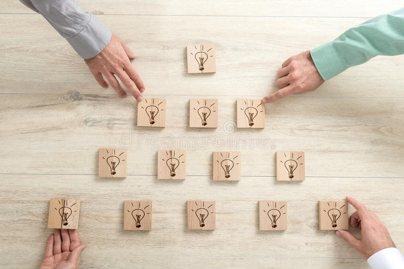 Four business people placing wooden blocks with light bulbs in a royalty free stock photo