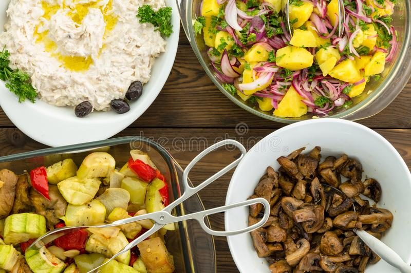 Overhead view of four savory vegetable dishes. Set on a wooden table with stainless steel tongs and spoon royalty free stock image
