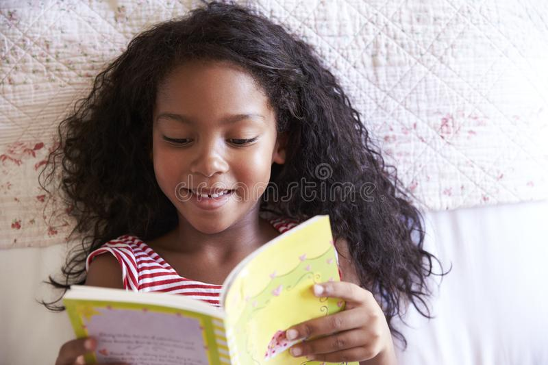 Overhead View Of Girl Lying On Bed And Reading Book royalty free stock photo