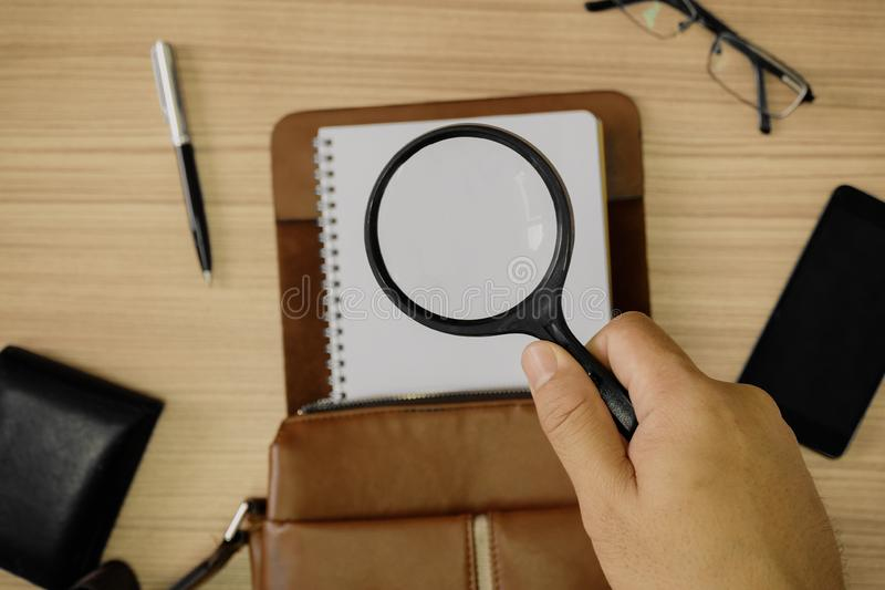 Hand Holding Magnifying Glass Over Notepad and Satchel Leather Bag royalty free stock photography