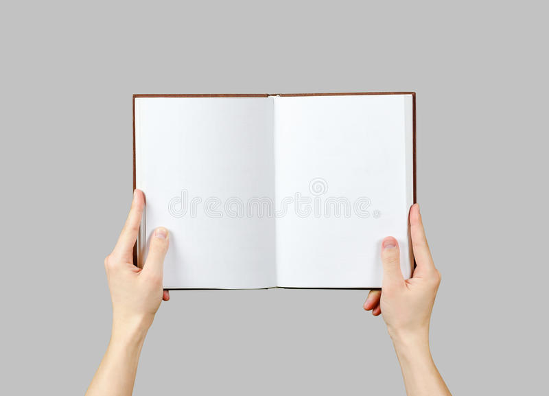 Overhead view of hands holding a blank book ready with copy space ready for text. Isolated on grey background. With clipping path royalty free stock images