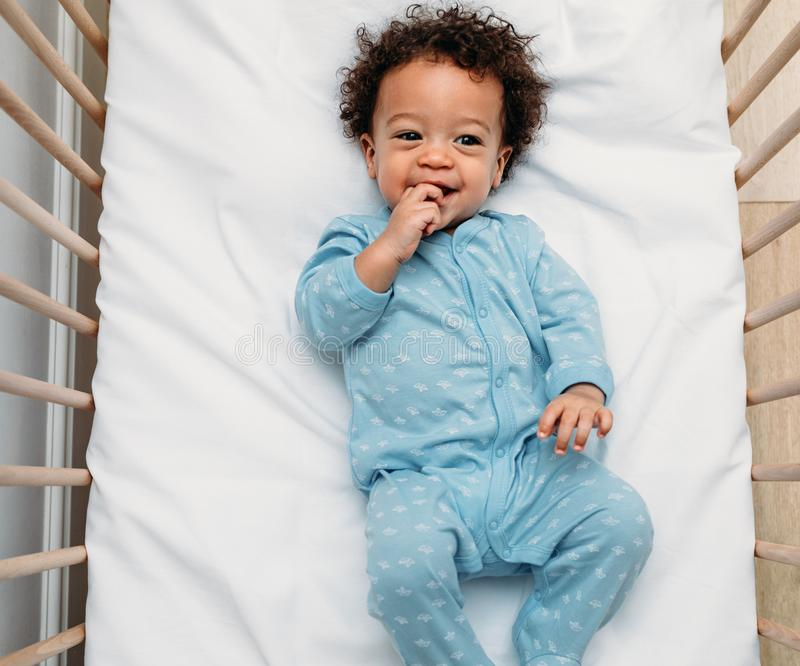 Overhead view of a happy baby boy lying in a crib stock photography