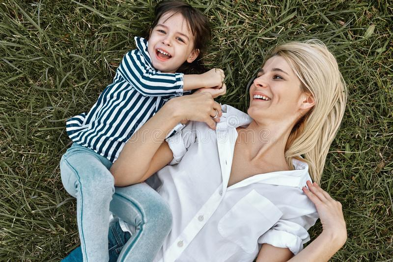 Overhead view of happy blonde woman playing with her cute little child, lying on green grass outdoor. Loving mother and daughter royalty free stock image