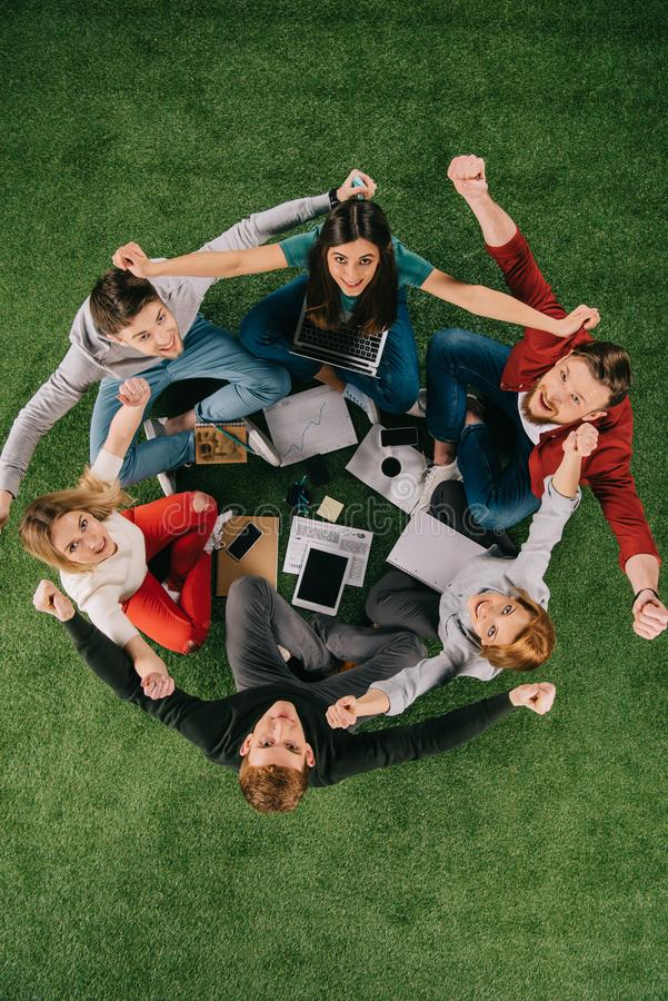 overhead view of happy businesspeople with arms up sitting stock photos