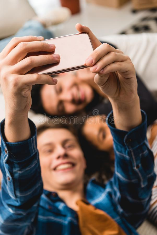 Overhead view of happy teens taking selfie while lying. On bed royalty free stock photography
