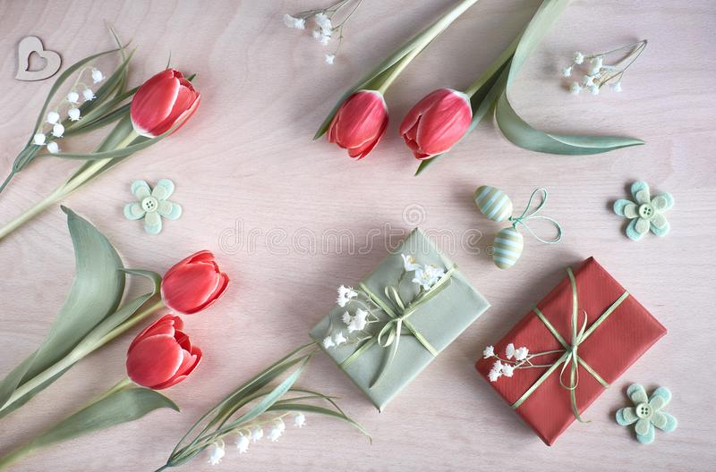 Overhead view of light wooden table with springtime decorations, wrapped gifts, white flowers, red tulips and and Easter eggs stock photos
