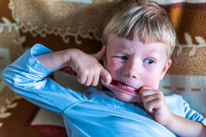 Overhead view little blond boy making silly face on sofa royalty free stock photo