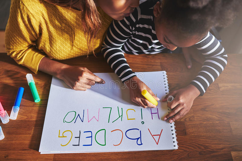 Overhead view of little girl learning the alphabet. Using coloured crayons stock images