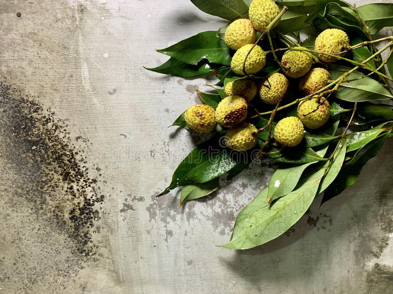 Overhead view of lychees with green leaves and drops of water on a rustic background, Food photography. Overhead view of fresh lychees with green leaves and stock photo
