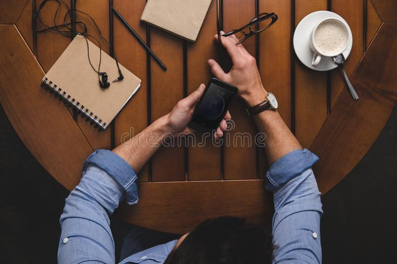 Overhead view of man using iphone at wooden table with coffee. And notepads royalty free stock image