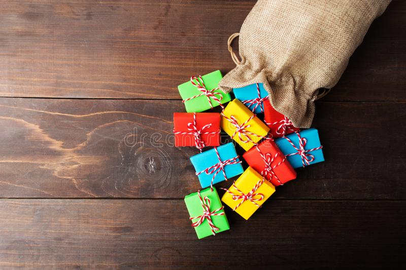 Overhead view of material bag with scattered colorful gifts stock photo