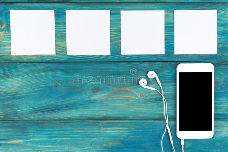 Overhead view of mobile phone with screen and in-ear headphones and white empty blank sheets on black wooden table,. Floor. Empty space for text, copy space royalty free stock photo
