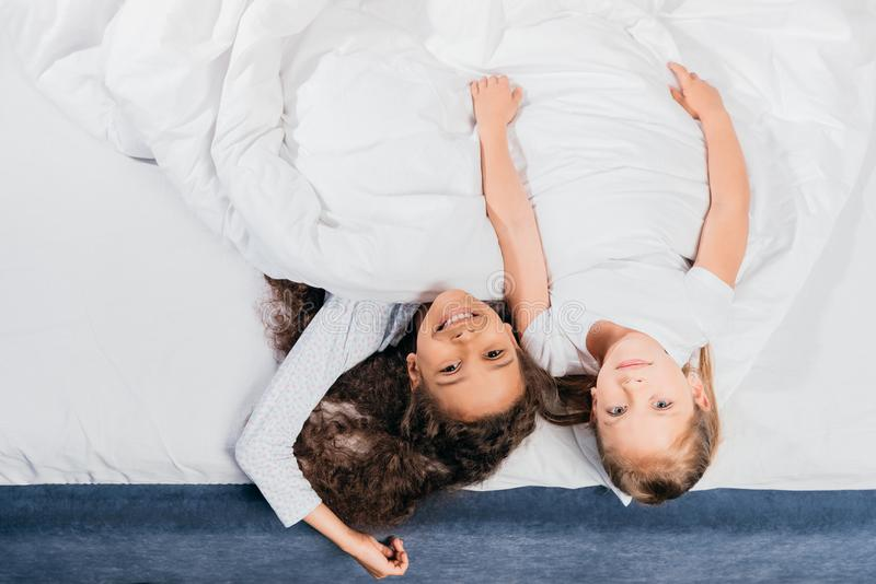 overhead view of multicultural adorable girls lying in bed at home royalty free stock photos