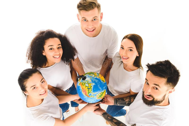 overhead view of multicultural group holding globe and smiling while standing in circle isolated royalty free stock photo