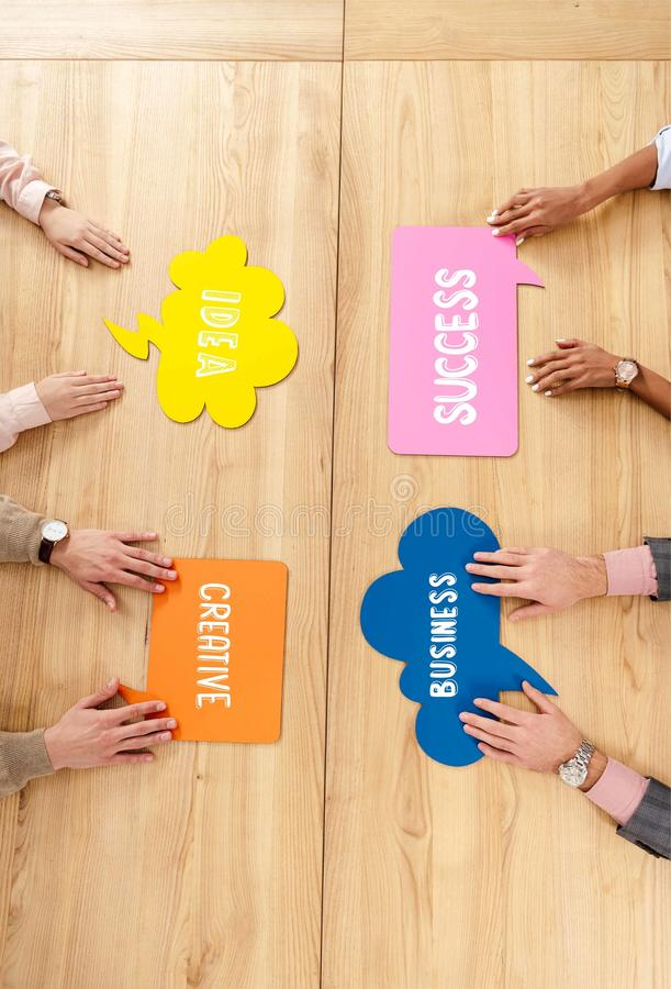 overhead view of multiracial business people at wooden table with colorful chat bubbles with success, idea, creative, royalty free illustration