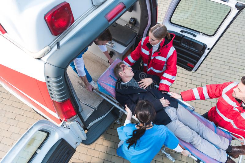 Overhead view of paramedic team moving injured man. Overhead view of paramedic team moving injured men on ambulance stretcher into car royalty free stock photo